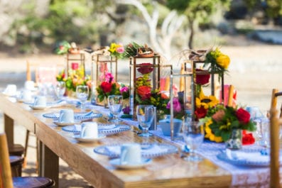 long wooden table and chairs setup with colorful flower decoration for breakfast at Ayo rock formations