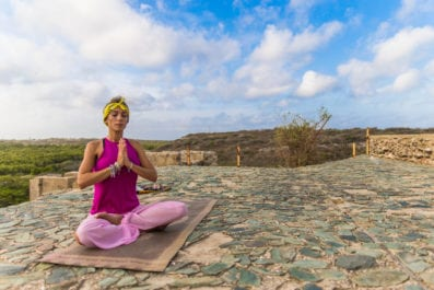 A lady in pink sitting in a yoga pose with her eyes closed on a clear and sunny day.